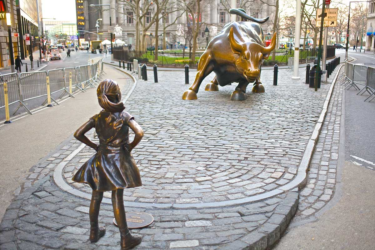 statue of girl facing off against Wall Street Bull in New York City