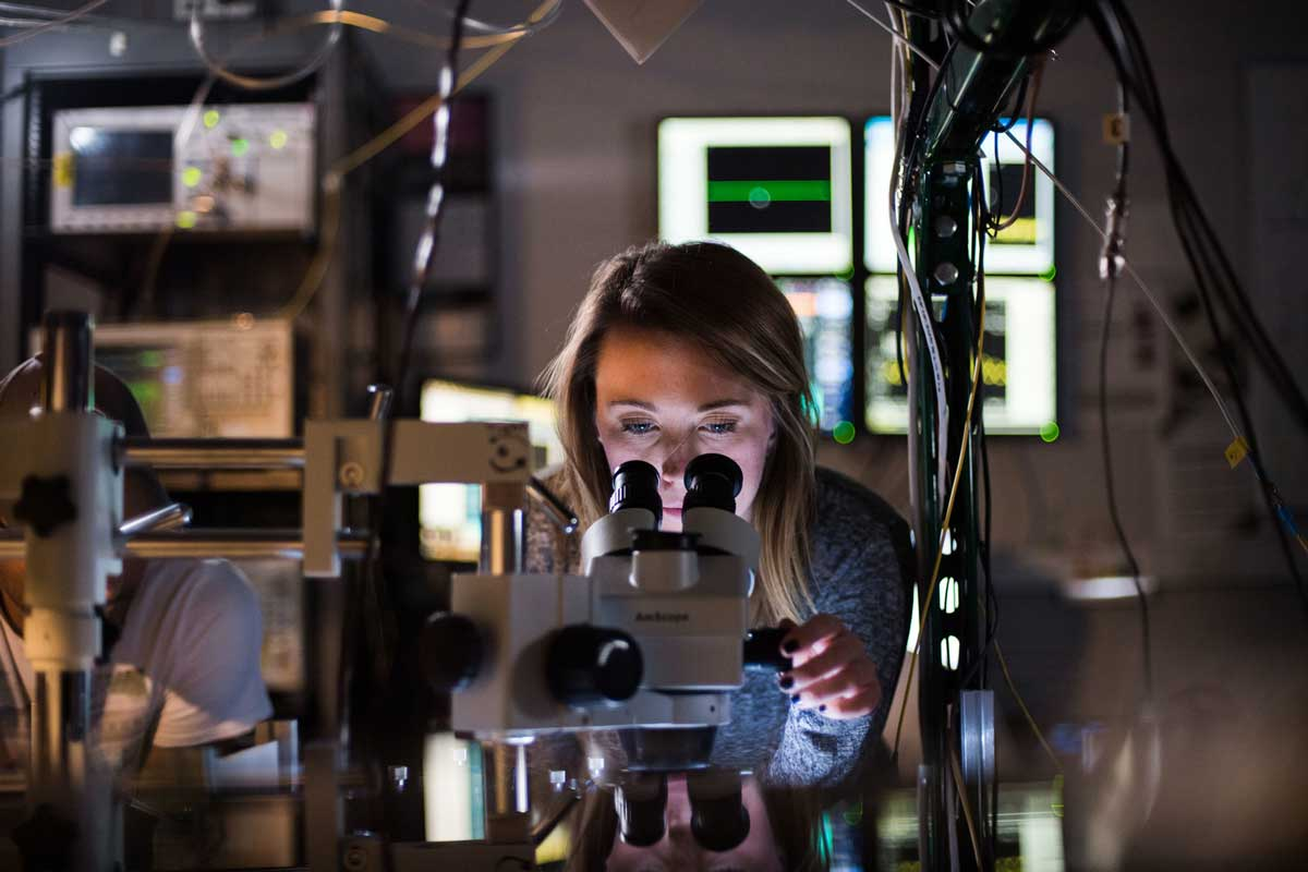 Blonde woman looks into a microscope in a lab