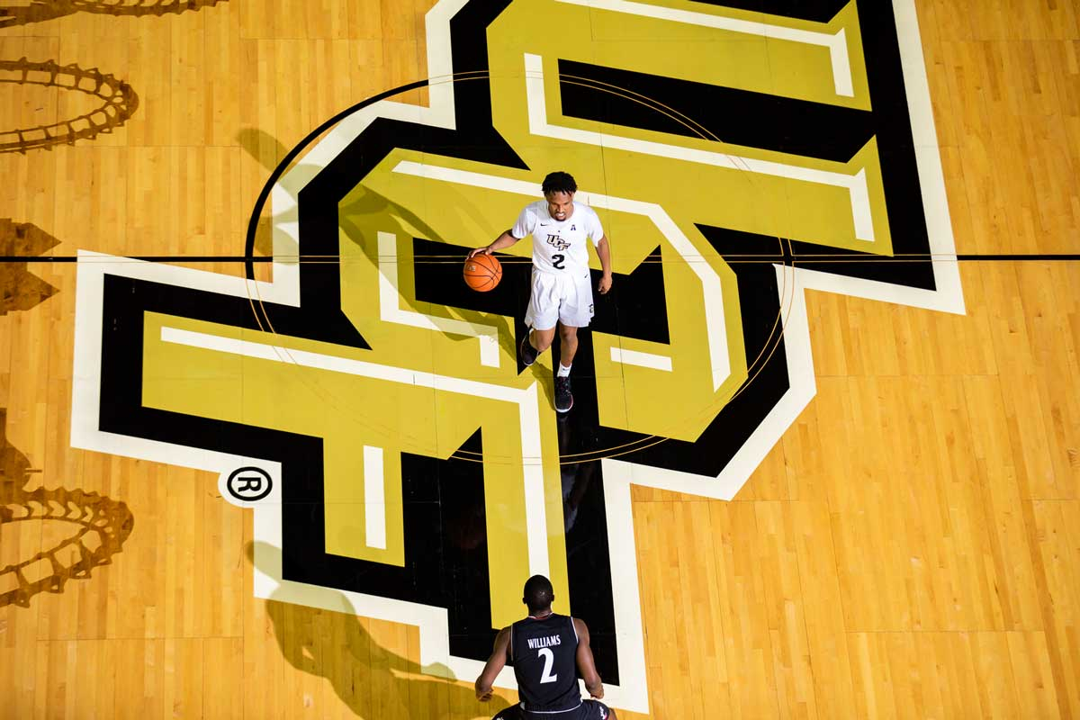 basketball player wearing white uniform dribbles ball across half court with UCF logo on floor