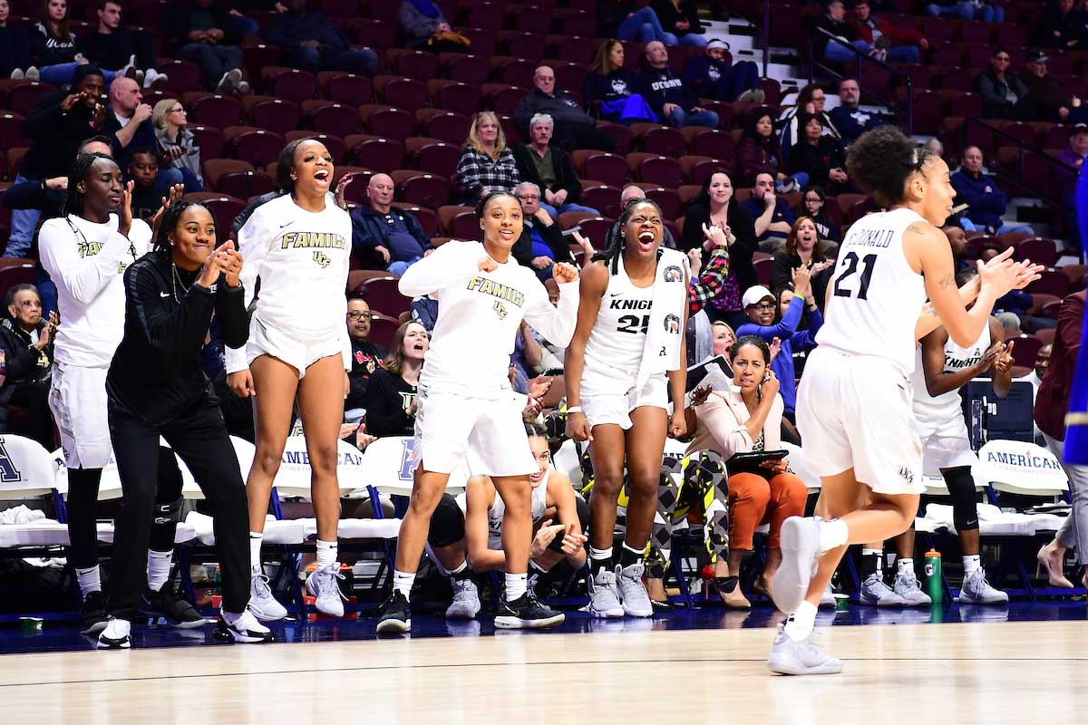 women's basketball players cheer on team bench