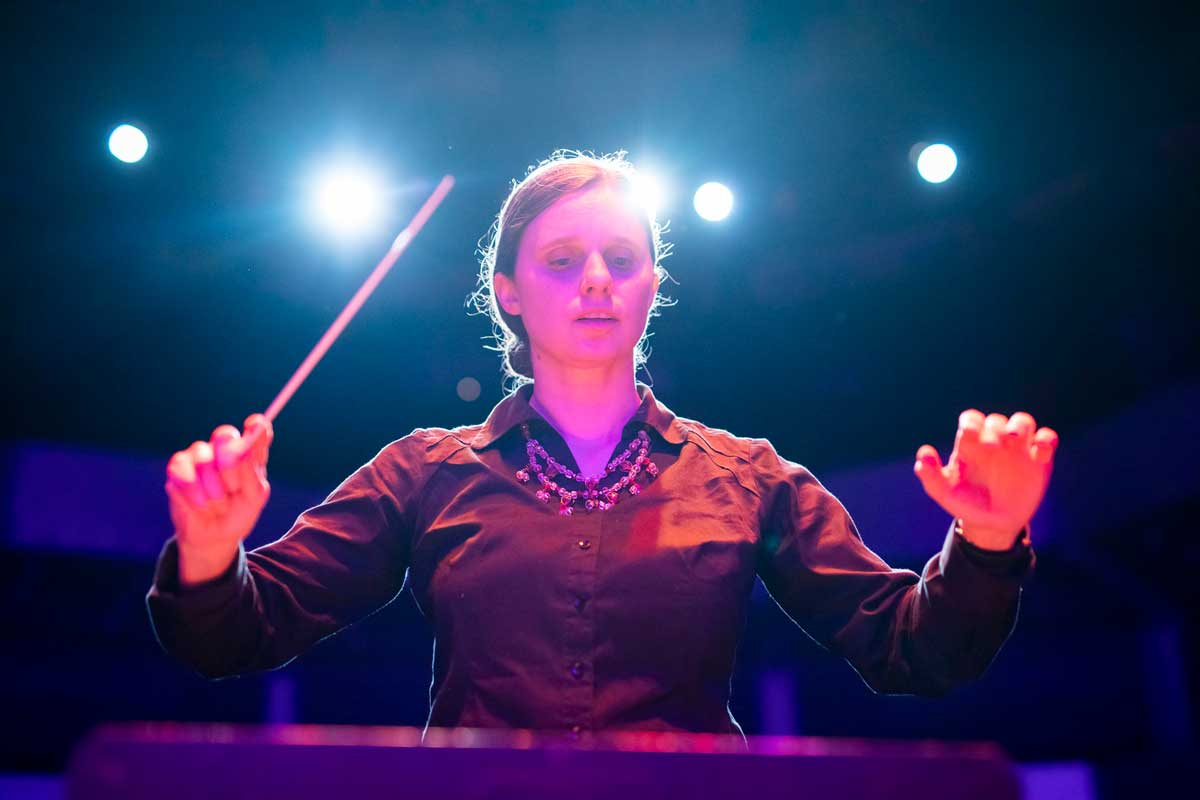 Woman in black long sleeve shirt holds conducting baton on stage with lights behind her