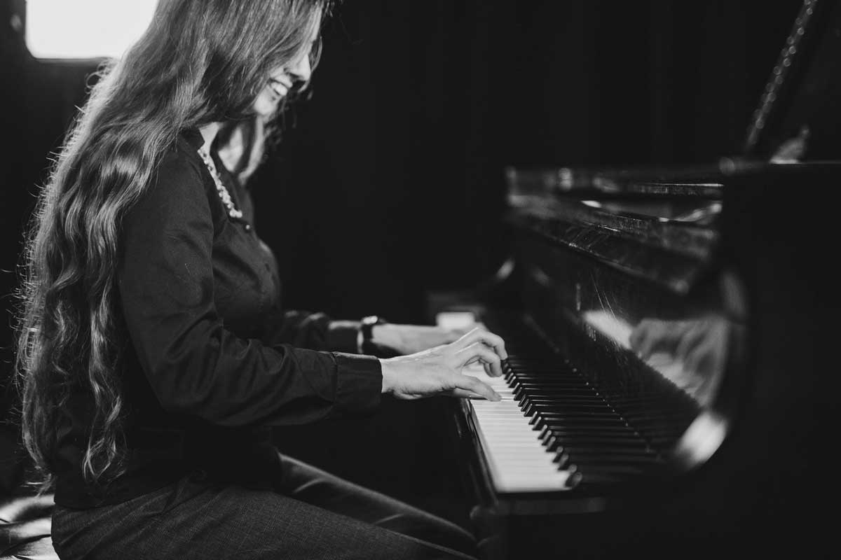 black and white photo of woman with long hair playing piano