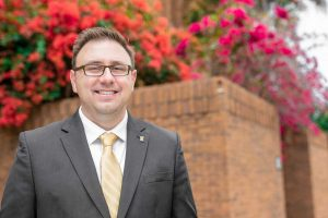 Man wearing glasses and gray suit with yellow tie stands in front of brick flower bed