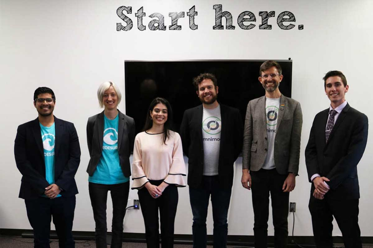 Six individuals stand in front of white wall with decal: Start here.