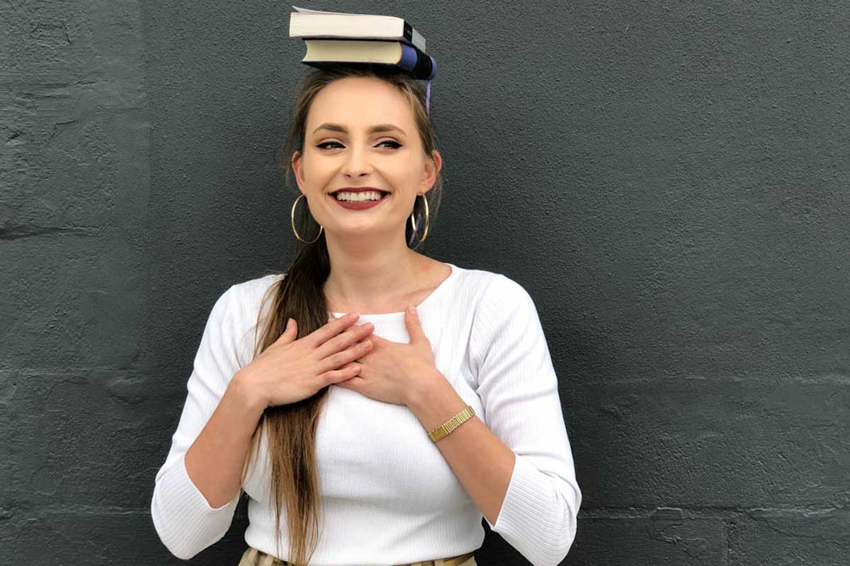 Young woman wearing white long sleeve shirt balances two books on her head