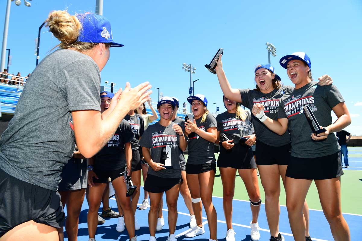 women's tennis team celebrates with trophies on court