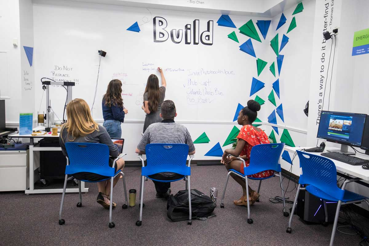 Students draw on whiteboard in classroom