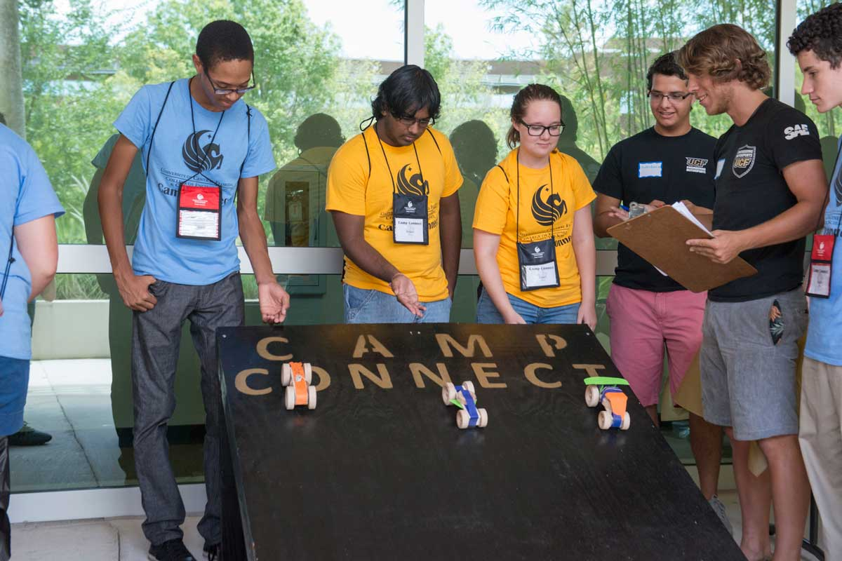 Three students release boxcar races down a black ramp