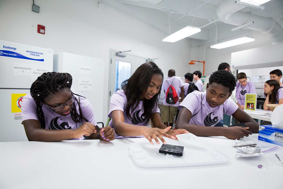 Three students in purple shirts sit at a white table