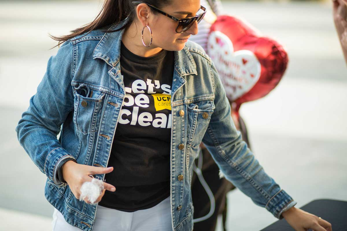 Woman wearing denim jacket and Let's Be Clear black t shirt looks down