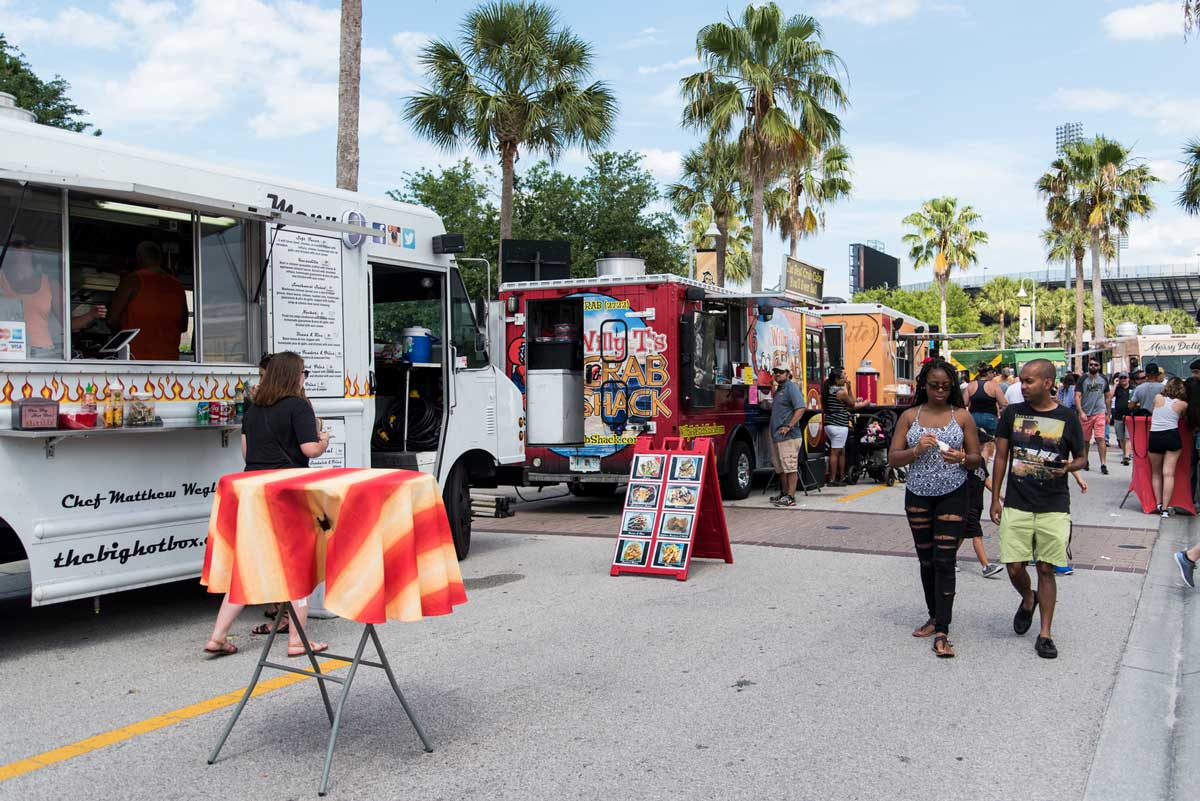 Food trucks lined up on a street with palm trees in background on sunny day