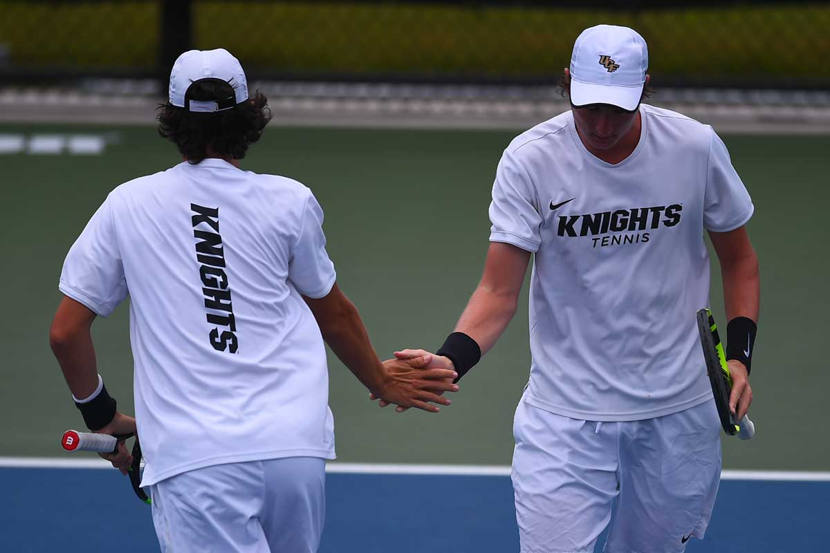 two tennis players high five on court