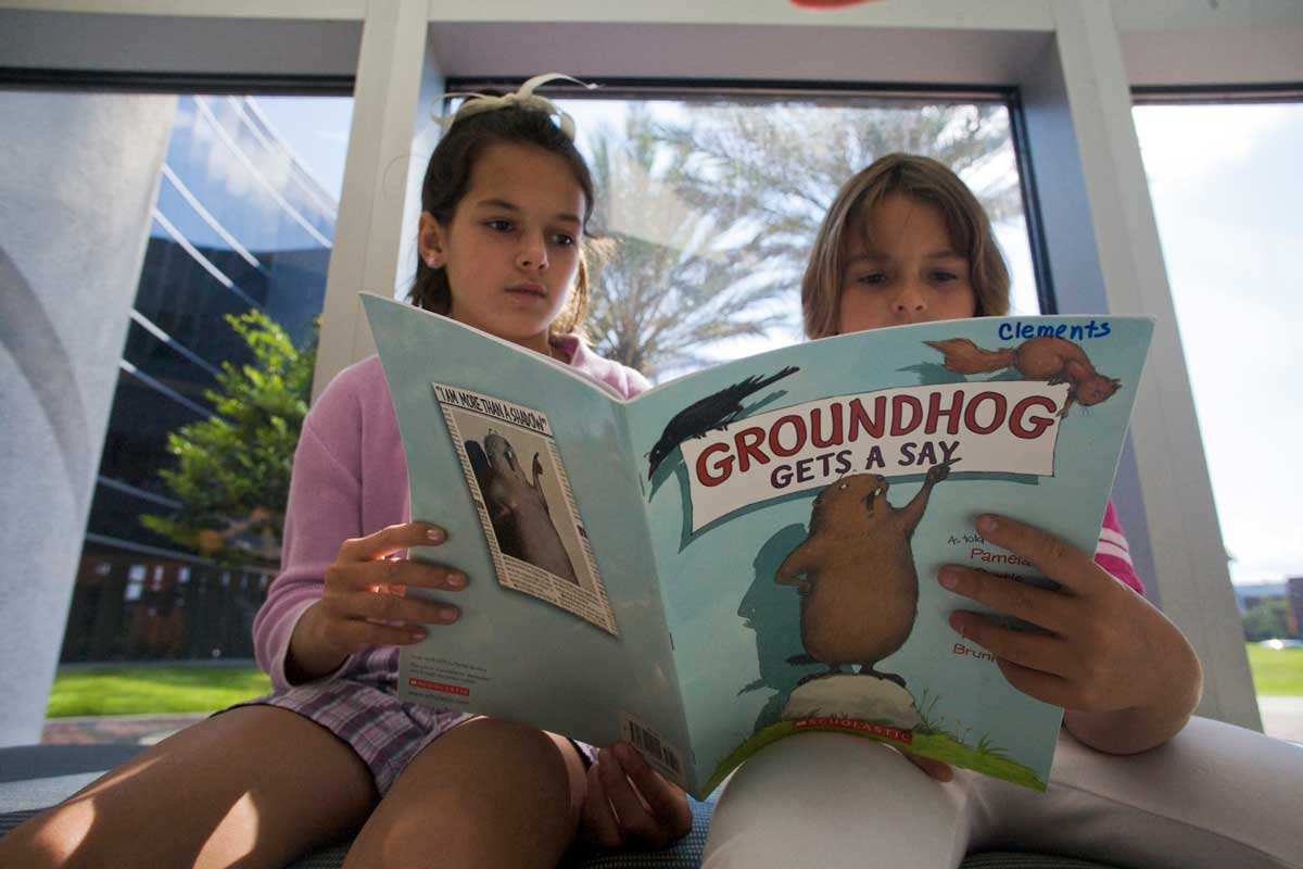 "two children read ""Groundhog Gets a Say"" book in front of window"