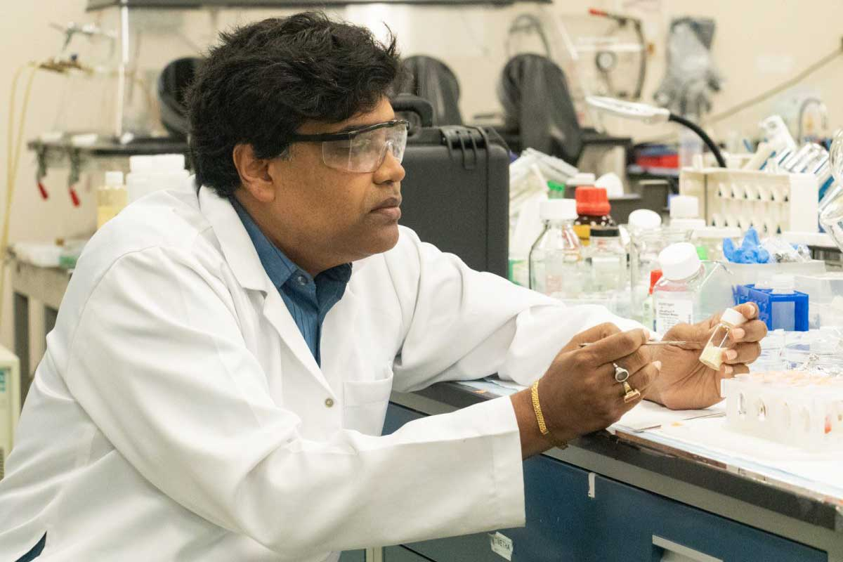 Man in white coat and protective glasses sits at a lab bench