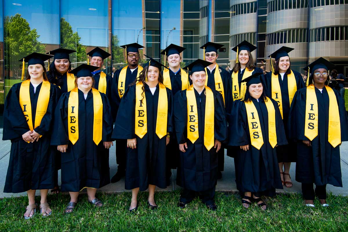 13 students wearing black cap and gowns and gold stolls stand in front of glass building