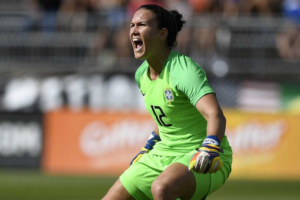 Female goalkeeper in green uniform yells