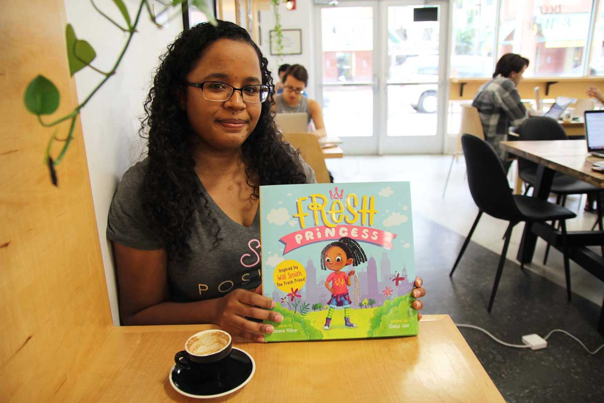 Woman with dark, long hair, sits at a wooden table with a coffee mug and holds up children's book