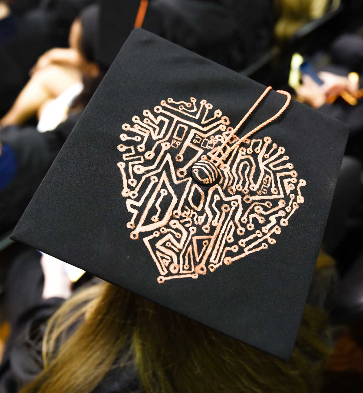 Grad cap decorated with gold heart made of intricate lines