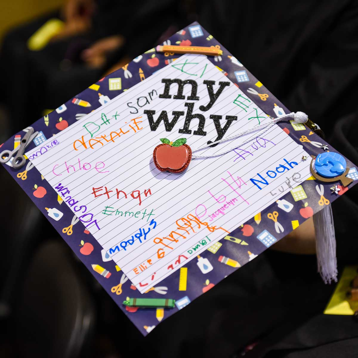 Grad cap decorated with children's signatures on notebook paper