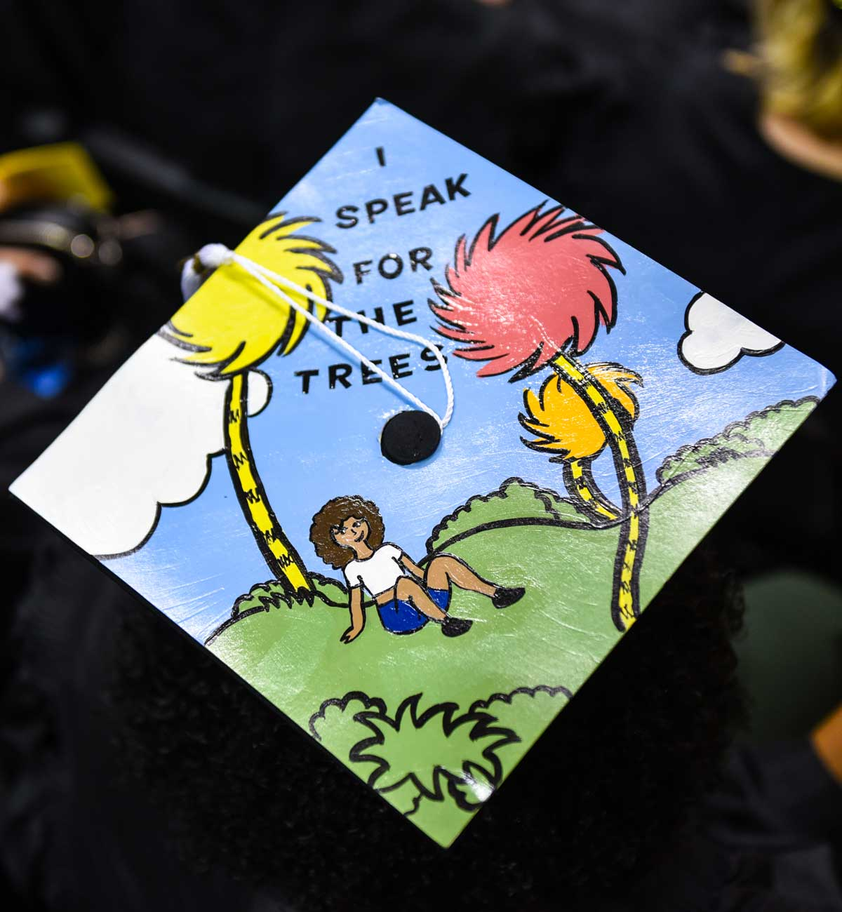 Grad cap decorated with text: I speak for the trees
