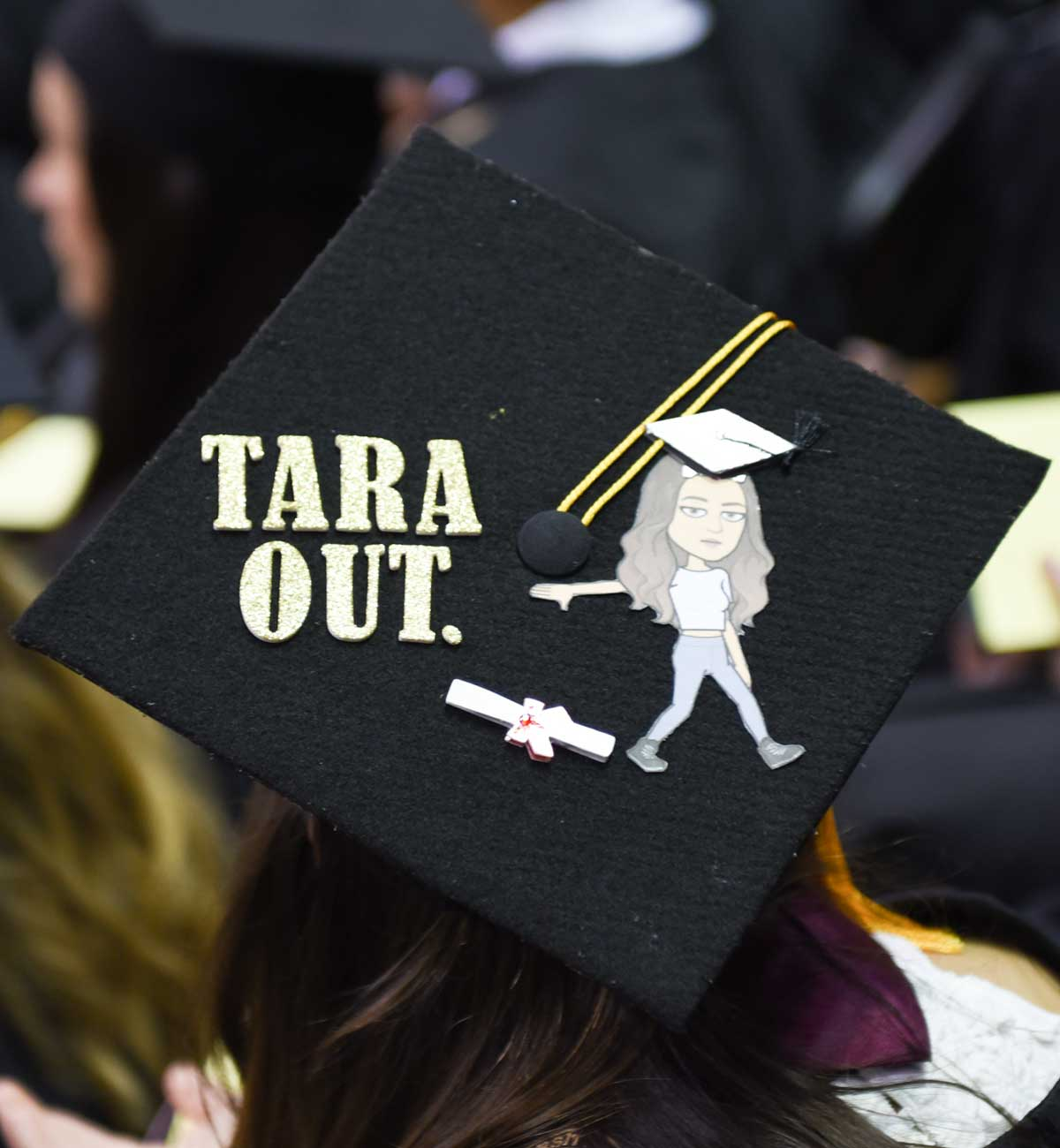 Grad cap decorated with text: Tara Out and image of person dropping diploma