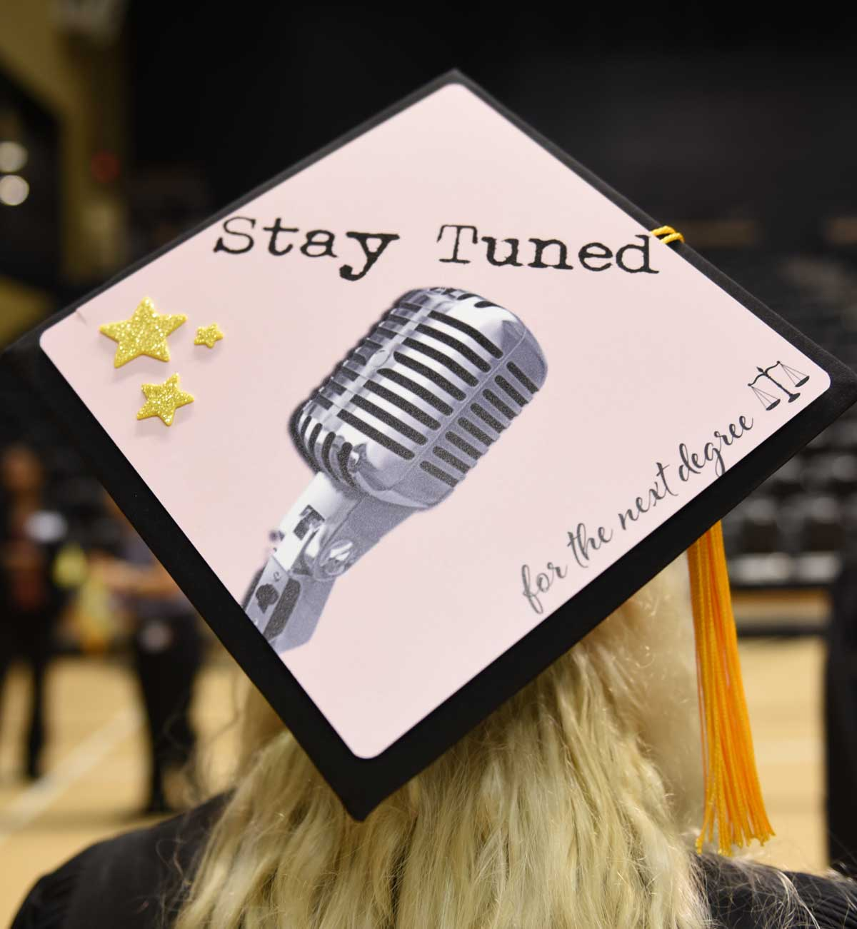 Grad cap decorated with microphone and text: Stay tuned