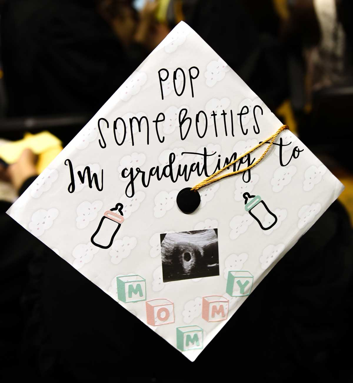 Grad cap decorated with text: Pop some bottles, I'm graduating to Mommy