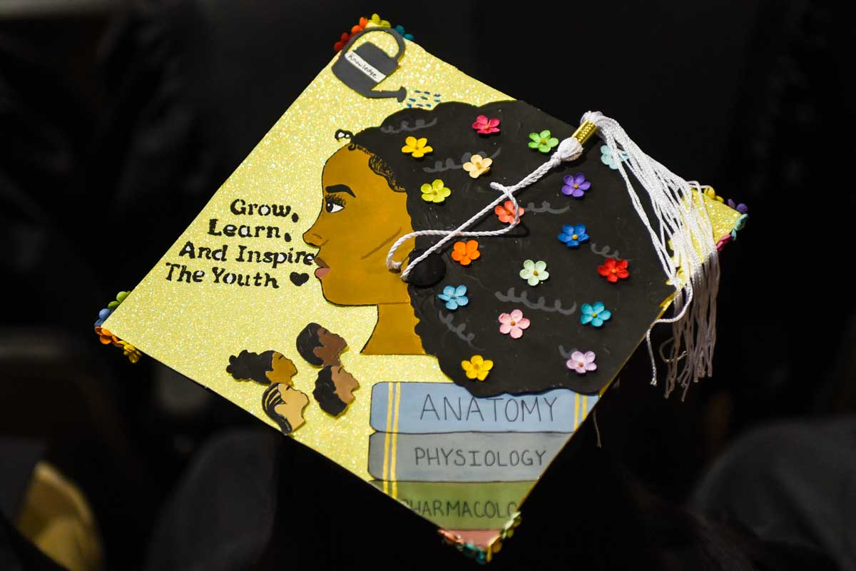 Grad cap decorated with African-American woman's face and flowers in her hair and text: Grow, Learn and Inspire The Youth