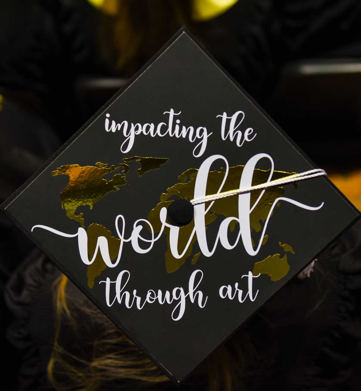Grad cap decorated with text: Impacting the world through art