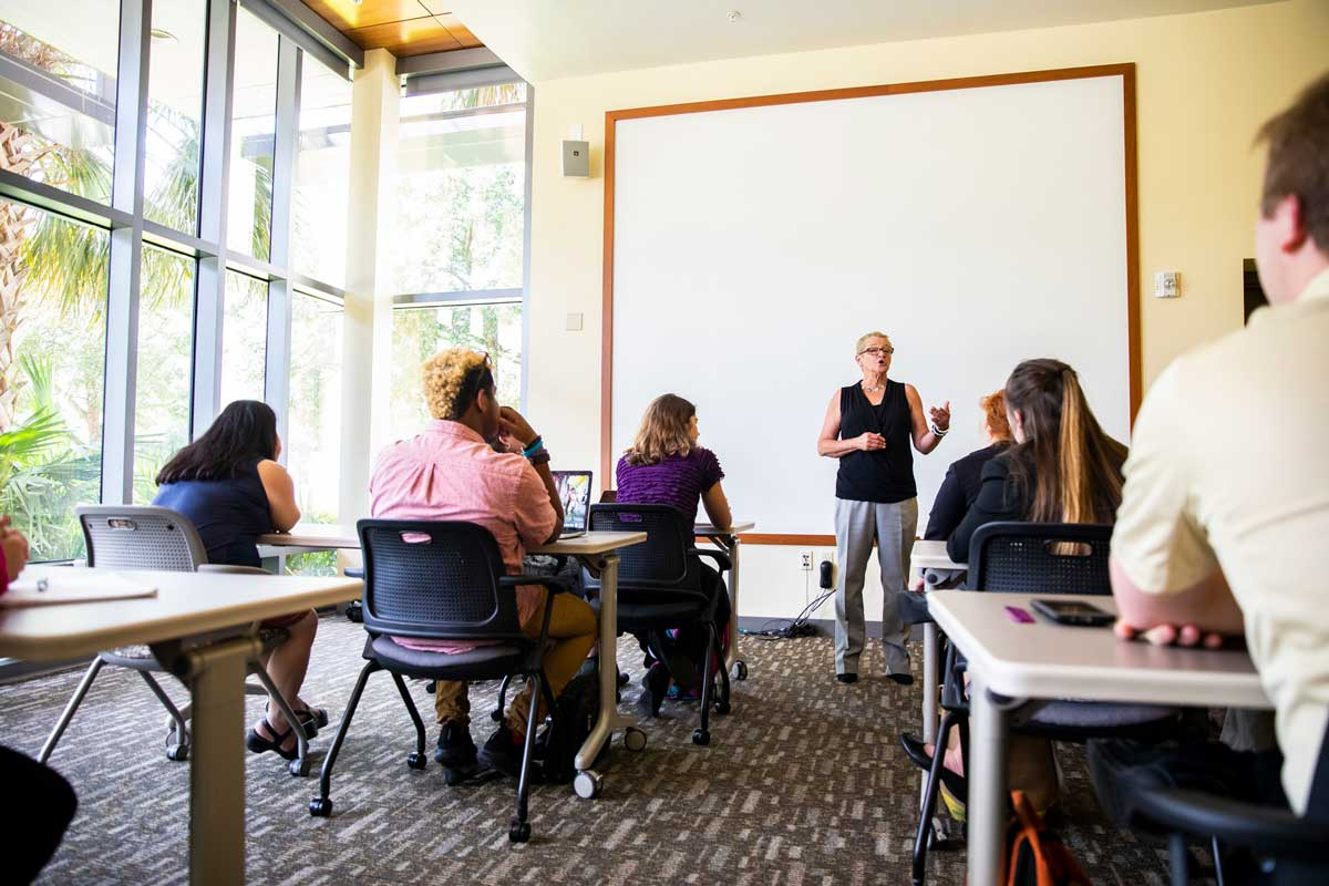 Woman stands at front of classroom in front of blank screen with students sitting at desks in front of her
