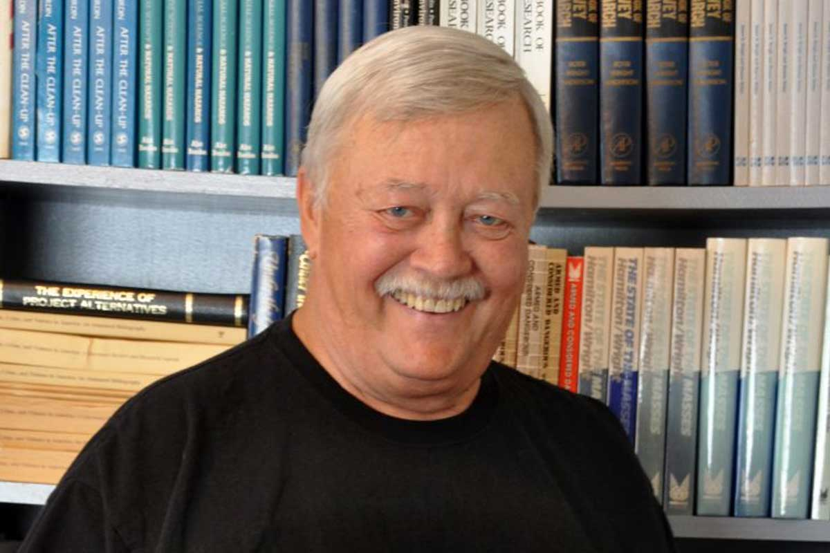 Man with gray hair and mustache stands in front of book shelf