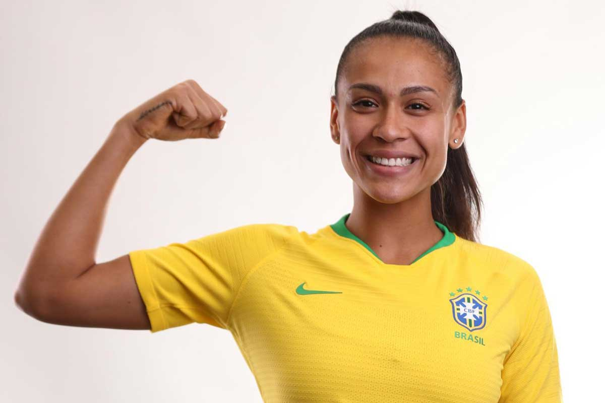 Female soccer player flexes muscle while wearing yellow jersey