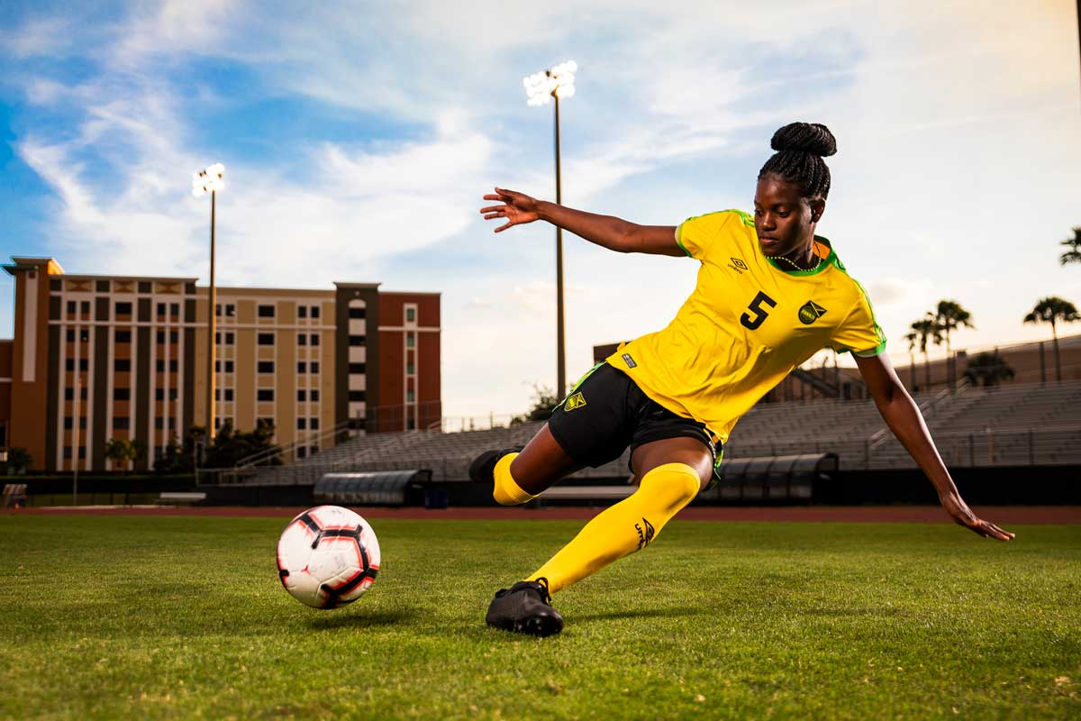 Female soccer player in Jamaica uniform prepares to slide tackle a soccer ball on field