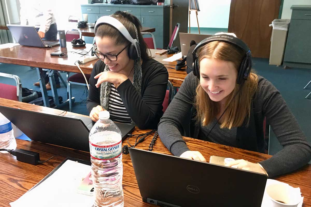 Two women with headphones on sit at a desk in front of laptops