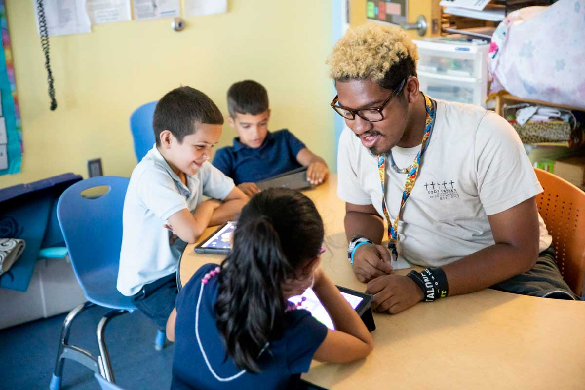 Adult male sits at a table in a classroom with three children holding digital tablets
