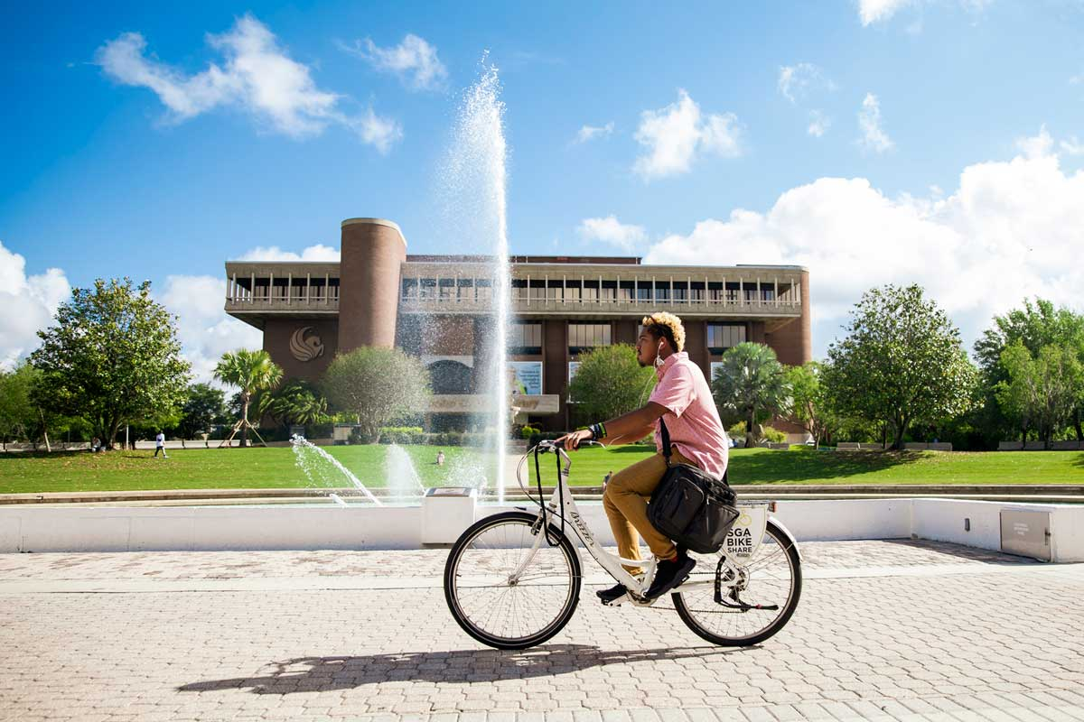 Man rides a bike near a fountain
