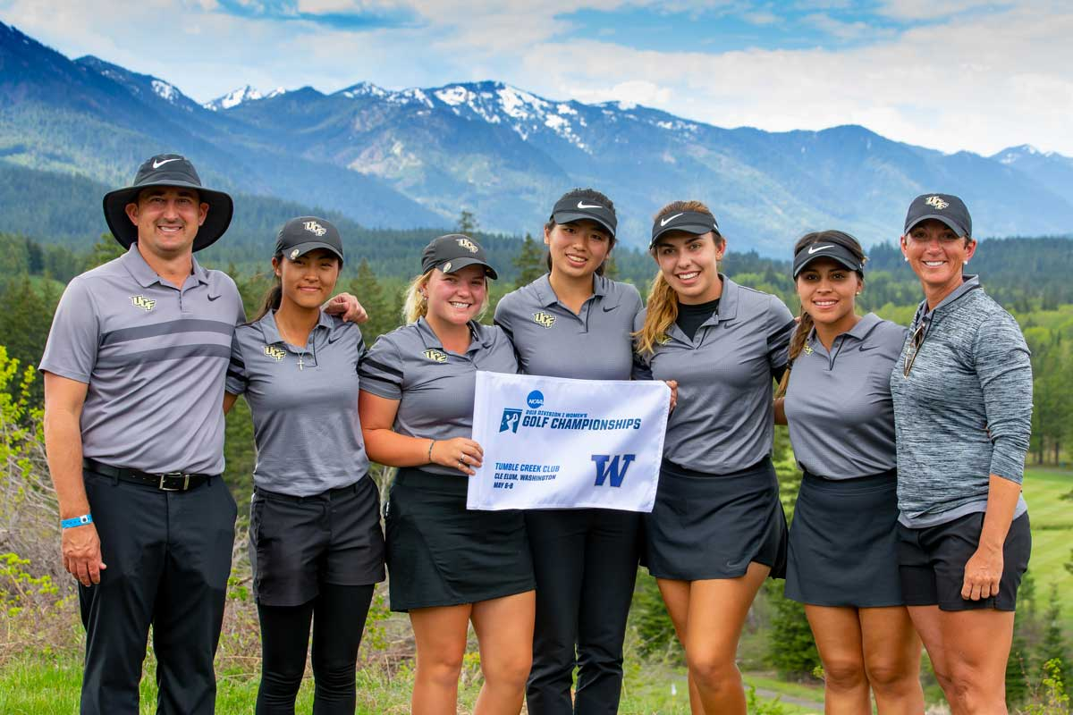 UCF women's golf team poses, arms linked, in front of mountain backdrop