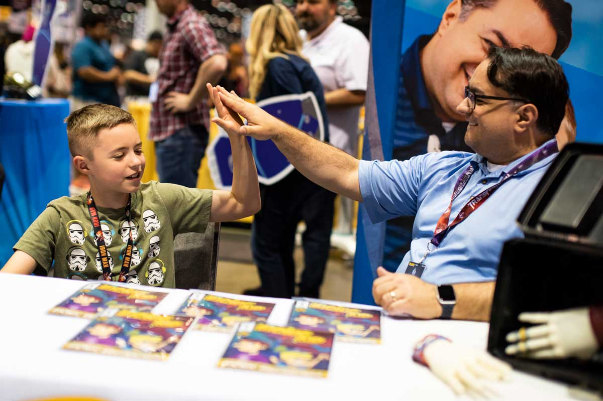 Father and son high five while sitting at a white table with comic books displayed on it.
