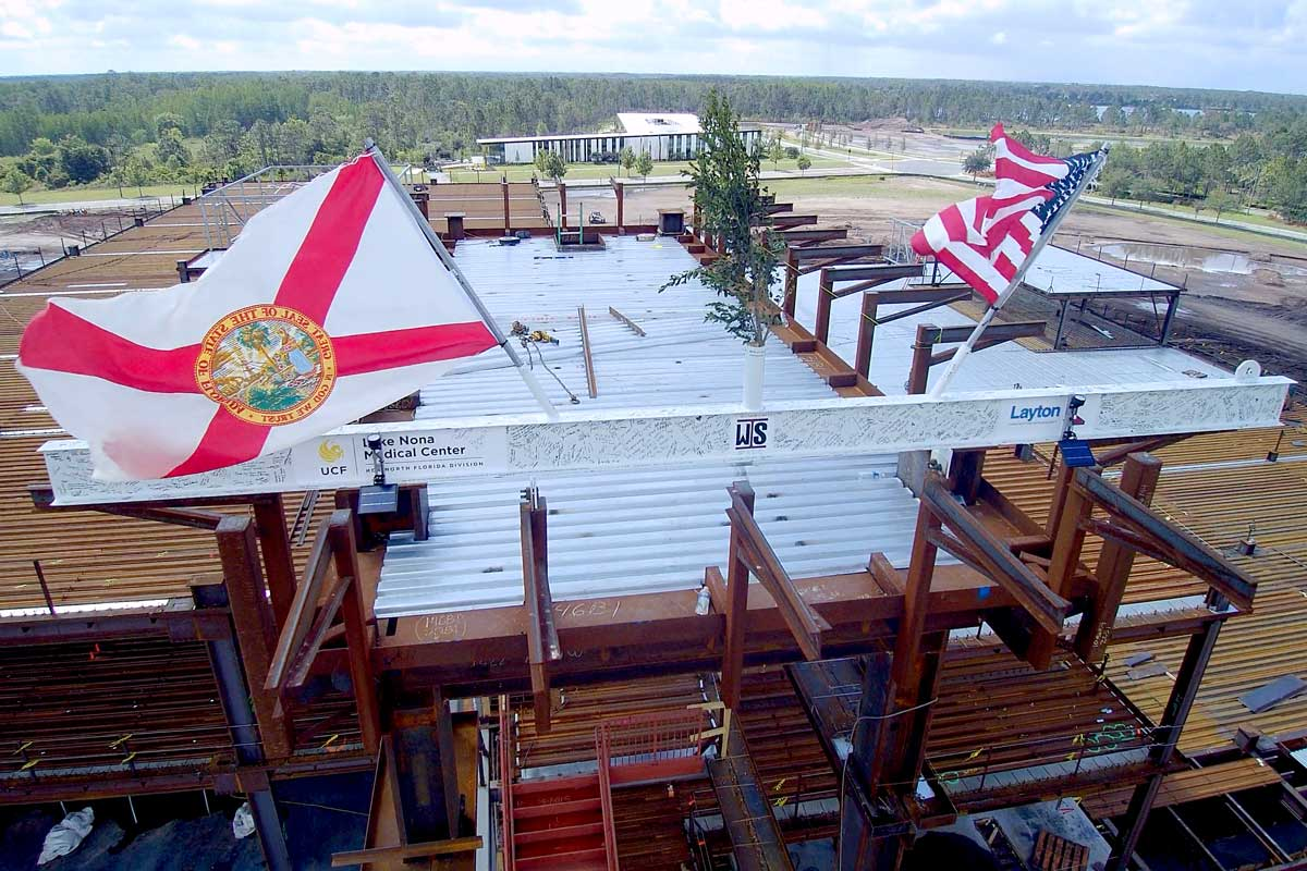 White beam sits atop construction framework with U.S. and State of Florida Flags waving atop the structure