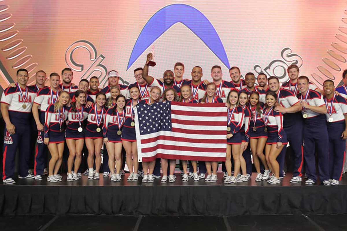 cheerleaders stand on stage holding American flag