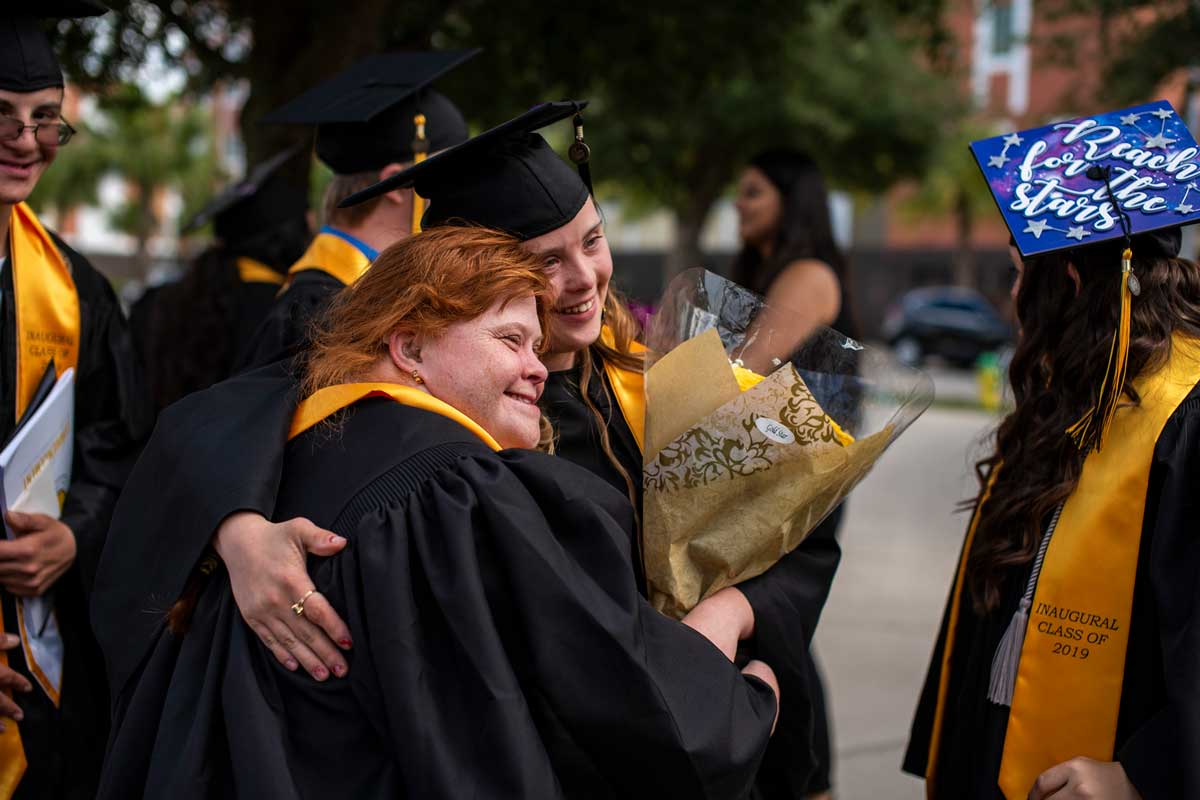 Two graduates in black caps and gowns side hug