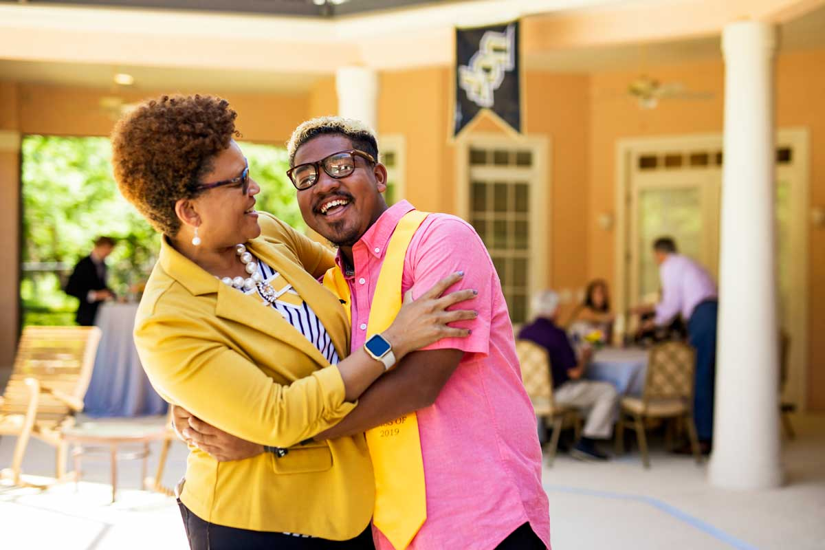 Woman in yellow jacket hugs her son, who is wearing a pink shirt and yellow graduation stoll