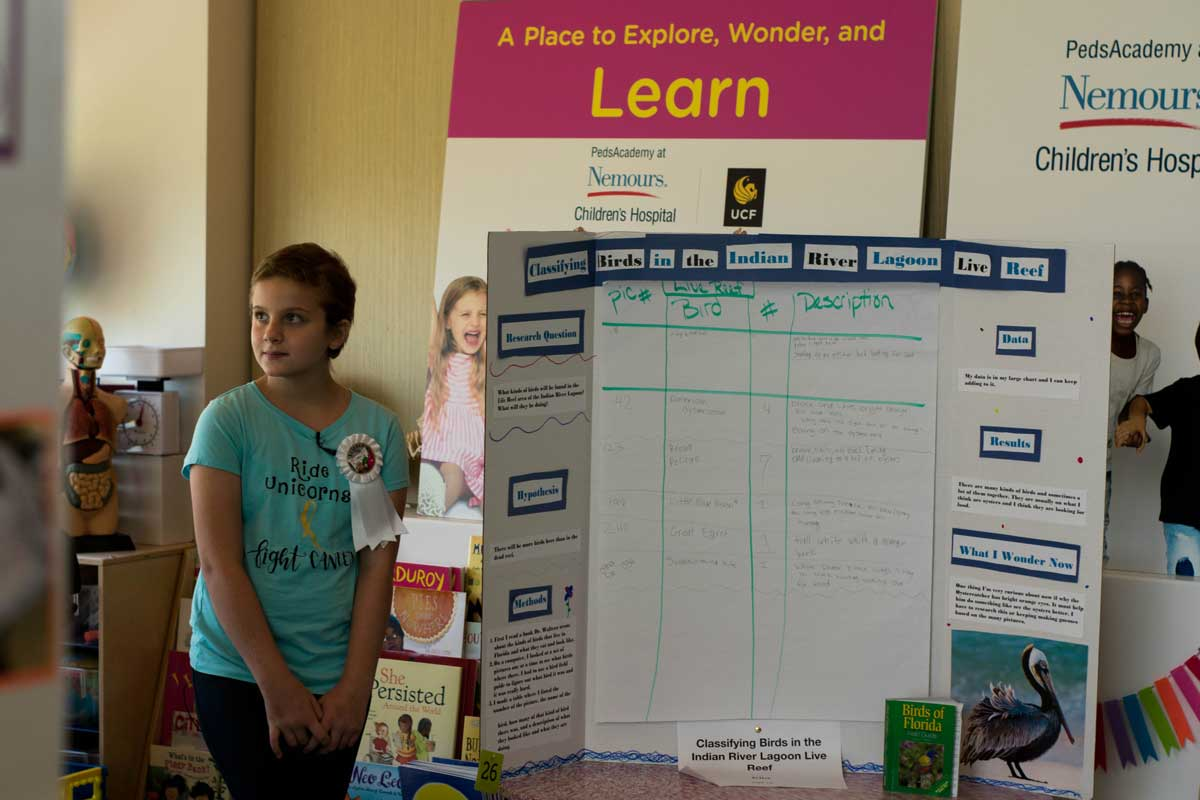 Young girl wearing a blue shirt stands next to science board display