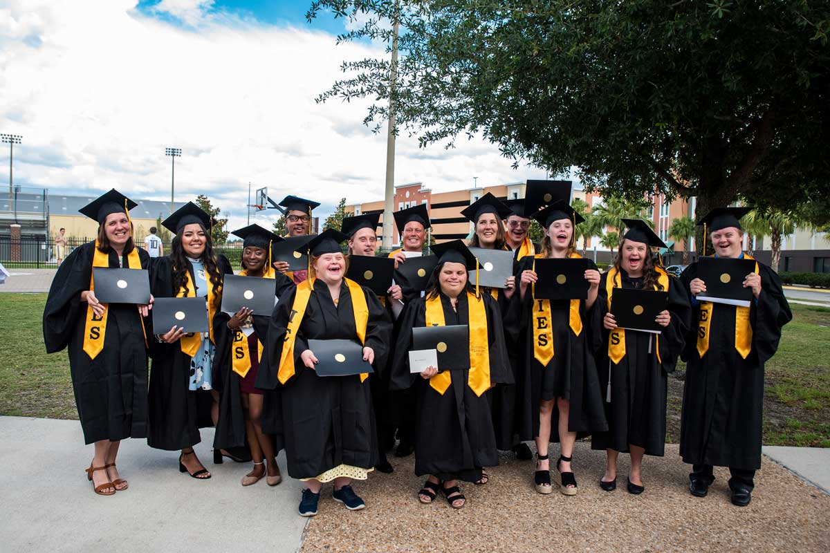 Group of 13 graduates in black cap and gowns