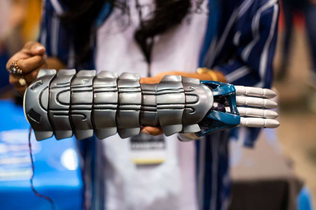 Woman holds gray prosthetic arm