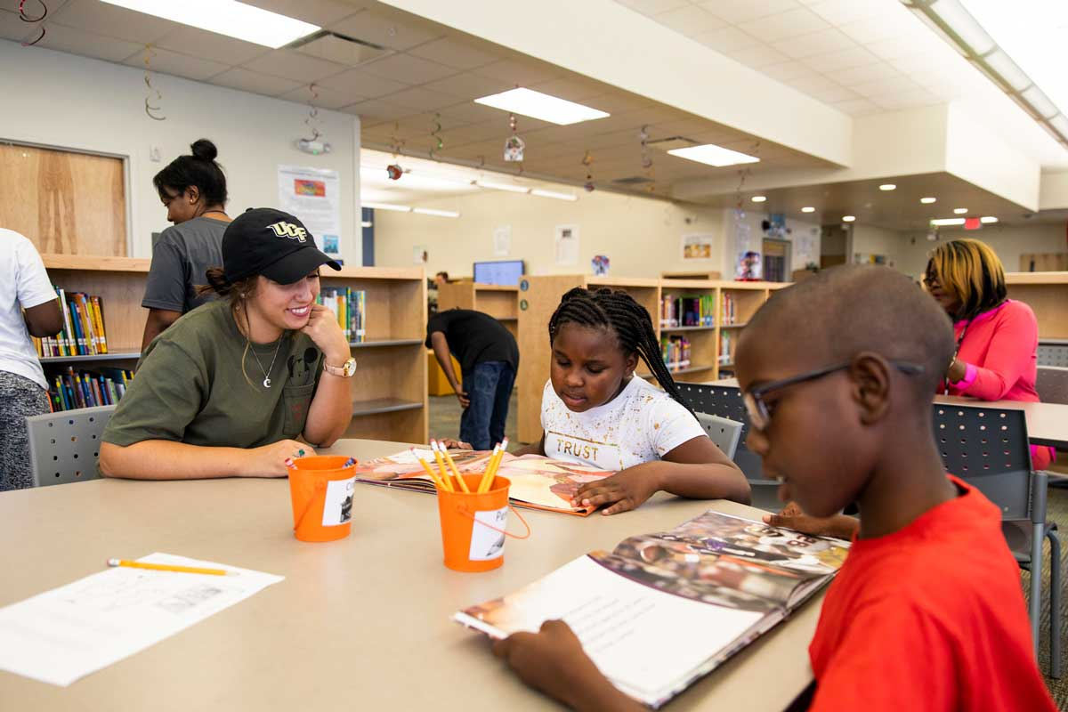 College student wearing a baseball cap and green shirt sits with two children reading at a table