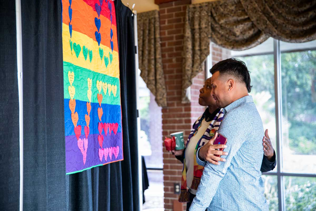 Two people stand in front of a rainbow colored quilt with L-O-V-E stitched in hearts