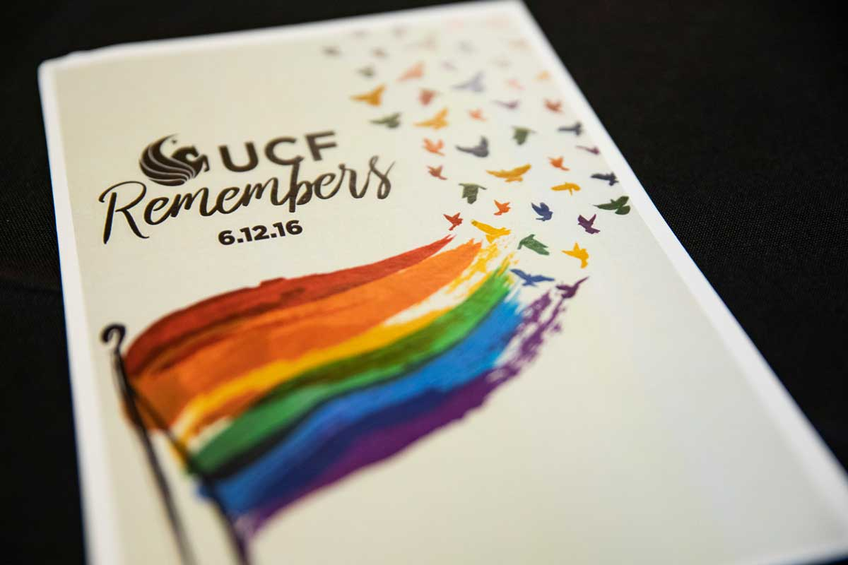 """white paper with rainbow flag that reads """"UCF Remembers 6.12.16"""""""