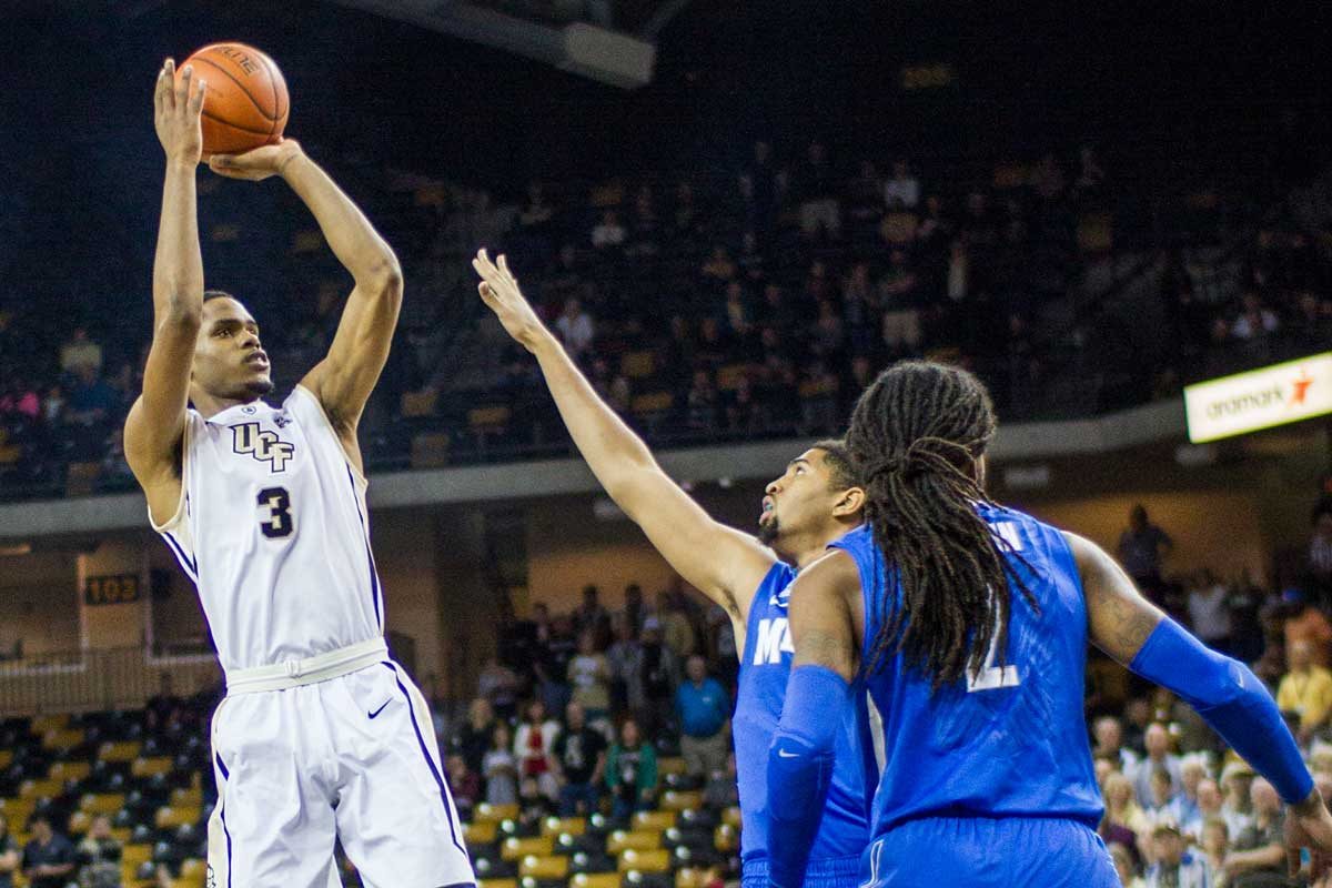 UCF basketball player AJ Davis pulls up for a jumper with defender coming at him