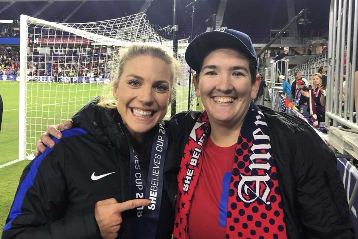 U.S. women's national team player Julie Ertz poses with Ashley Taylor, a fan dressed in red shirt with a red scarf and hat, near soccer field